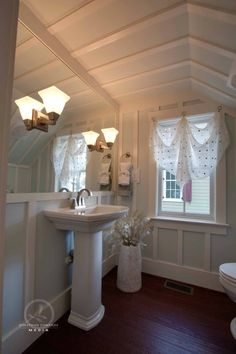 Half-bath underneath staircase. Board and batten taken all the up the walls and ceiling.