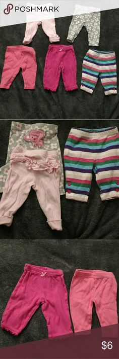 5 pairs of pants All 100% cotton. Carter's, Child Of Mine from the makers of Carter's, and Just One You made by Carter's brand. Gray pair: white flowers with pink centers and pink elephant on back. Light pink pair: folded hem and ruffle on back. Multi color striped pair has 2 buttons near bottom on legs. Coral pair has a slightly scalloped hem. Dark pink pair has a bow on front and ruffles on bottom hem. Good condition, gently used Bottoms Casual