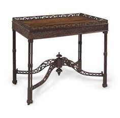 To me, this is the most beautiful piece of furniture I've ever seen.... A GEORGE III MAHOGANY SILVER TABLE  CIRCA 1760  With a pierced gallery above a blind fret-carved frieze, on circular cluster legs, on leather casters  30 in. (76 cm.) high, 35½ in. (90 cm.) wide, 22½ in. (57 cm.) deep