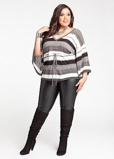 slim fit jeans tucked into high heeled knee high boots exaggerate leg length. Sleeve cuts of just above wrist emphasising narrowest  part of arm. Bold tonal stripes work to break up upper body. Wear with confidence!!!!!!!!!11