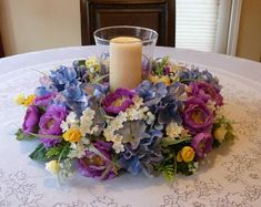 This spring candle centerpiece was made on a 12 inch grapevine base with blue hydrangeas, purple ranunculus, yellow spray roses and babies breath. An assortment of pretty greenery and a cute bird adds the finishing touches.