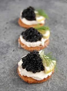 Three black caviar appetizers with cream cheese, lemon and dill.