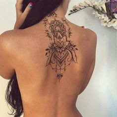 Dainty elegant floral back tattoo.