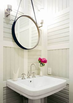 Thom Filicia small powder room with black leather mirror, white pedestal sink, sconces and paneled walls.