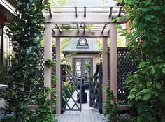 A pergola separates this city driveway from the classically appointed backyard. The Chippendale-style gate riffs on the trellis detail and leads the eye onwards to the Mansard-roof topped garden shed.