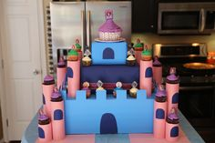 Cupcake castle stand made out of cardboard and covered with poster board. Towers made out of empty cans taped together her and covered with construction paper.