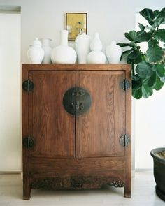 Beautiful antique Chinese chest with a minimal collection of white vases and a fiddle leaf fig. done.