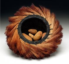 "Christine Love Adcock, Artist, Sunrise Nest Basket,  coiled basket of dyed palm fiber and river rocks,9""WX3""H"