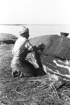 View of a man, kneeling, waterproofing a boat with pitch. Marshes, Iraq, by Thesiger, 1953