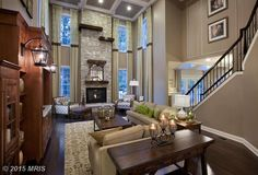Traditional Living Room with Box ceiling, Built-in bookshelf, Wall sconce, stone fireplace, Crown molding, High ceiling