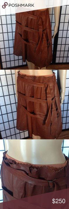 Jean Paul Gartier Leather Skirt w Belt Detailing Brown Leather skirt with triple belt detailing and a scattered design of small holes. Skirt is knee length and in a US size 6. From archive collection. Jean Paul Gaultier Skirts Midi
