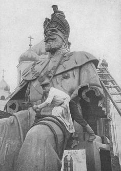 Russian revolutionaries destroying a statue of Tsar Alexander.