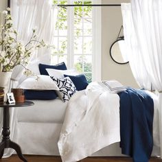 """Pale grey walls, white bedding and navy accents..... works well with wood or a black iron bed....."""