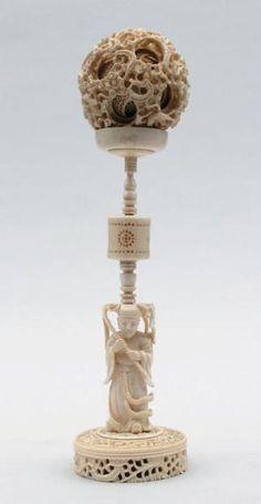 BOULE DE CANTON en ivoire ciselé, sculpté et ajouré à motifs de dragons, fleurs, feuillage et treillages composée de plusieurs sphères les unes dans les autres. Le support en ivoire à motif d'un personnage debout soutenant sur sa tête le piédestal.