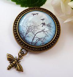 Diese romantische Brosche besteht aus antikgoldfarbenem Metall und einem handgearbeiteten Glas-Cabochon mit schönem Landschaftsmotiv.