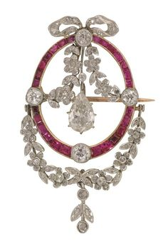 An Edwardian ruby and diamond laurel swag pendent. Set with an old pear shape-cut diamond, weighing approximately 0.75 carats, dropping by a rose-cut diamond-set floreal composition, to the centre of a calibre ruby-set oval, all set to a yellow gold mount with brooch fitting, comprising four millegrain-set old round brilliant-cut diamonds and including a rose-cut and old round brilliant-cut diamond-set bow to the top and a floreal composition to the bottom, all set in platinum, circa 1900.