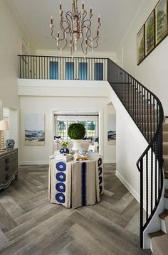 Glorious floors in a two-story home are admired as you walk down an iron and wood staircase into a foyer with a center table displaying unique and elegant decor. Foyer Decorating, Interior Decorating, Interior Designing, Decorating Ideas, Wood Floor Texture, Wood Staircase, Stairs, Staircases, Elderly Home