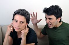 Man shouting and expressing anger towards woman who shuts her ears