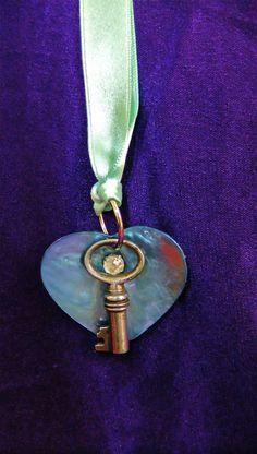 Cœur en nacre Bleu, strass et clef ancienne, sur ruban de satin vert lagon. 30 €