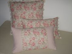 Cushions in Faded Roses and Majolica Stripe fabrics by Sarah Hardaker - with fan edge, pom pom, and decorative ribbon trims.