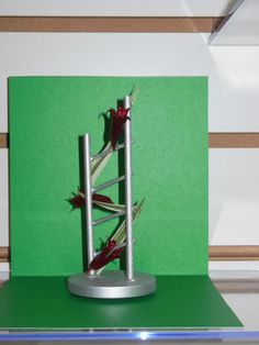 """""""Modern Mini,"""" blue ribbon @ 2013 Clay Co. Fair.  Dowels, toothpicks, and wood disc form the construction ladder.  Columbine pods and pressed ribbon grass.  Pods are painted with metallic nail polish. 5"""" design. Reflective and transparency qualities. By Jan Krass"""