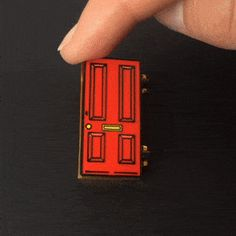 """This enamel pin is a door to space which opens and closes! • 1.25"""" • Secure black rubber clasp • Comes on a heavy weight linen finished backing card • Ships as a single pin on a backing card"""