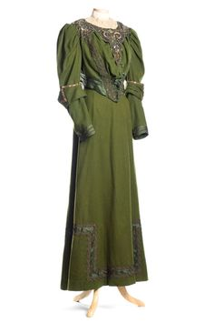 This forest green wool dress is a two-piece outfit – bodice and skirt. Both display the styling fashionable in the 1890s. It has the wonderful puffy sleeves and long, full but smooth skirt. The Gibson Girl look was popularized by Charles Dana Gibson through his many, often satirical, illustrations in newspapers and magazines. Our dress has elaborate trim of copper, green and silver beads and sequins on green net over green satin, along with bands of satin braid and ribbons.