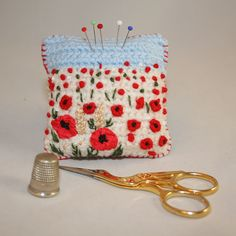 A pretty harvest scene of poppies in a cornfield on a crocheted background decorates the front of this pincushion. Poppies have been hand embroidered in a combination of silk ribbons, wools and threads. Ears of corn have been stitched in vintage thread. Poppy Pins, Ears Of Corn, Remembrance Day, Blanket Stitch, Blue Wool, Cotton Thread, Silk Ribbon, Pin Cushions, Wool Blend