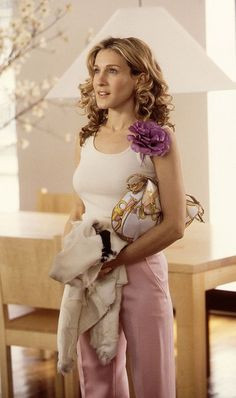 Carrie Bradshaw in white tank, pink pants, and purple floral brooch in Sex and the City