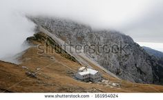 mountain hut (1864 m) near the wide saddle in Kamnik Alps in Slovenia. foggy clouds are forming just over the ridge to the north. by goodcat, via Shutterstock