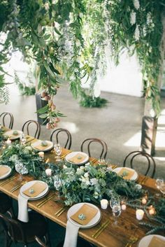 tablescape design, using slate and stone crockery, oatmeal linen napkins, personalised menus and individual succulents. Brushed gold cutlery sat on the exposed timber table with wild native foliage garlands running the entire 12 metre length of the table. #weddingtable