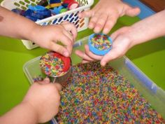 Sensory Play Rice and Bottle Tops: Developing fine motor skills through sensory play with rainbow rice and bottle tops that will also inspire the imagination and creativity. Sensory Activities Toddlers, Fun Activities For Kids, Sensory Bins, Sensory Play, Sensory Table, Indoor Activities, Preschool Arts And Crafts, Preschool Science, Science Experiments Kids