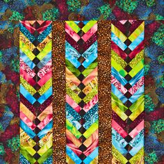 Columns of bright prints stand out against darker prints for a dramatic quilt. Black squares in the centers of the columns give the columns a braided look. Fabrics are from the Misty Light collection by Yuko Hasegawa for RJR Fabrics.