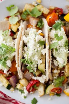 Roasted Veggie Tacos with Avocado Cream and Feta  Filling:  1 small zucchini, diced  1 small summer squash, diced  ½ medium red onion, diced  1 ear sweet corn, removed from cob  1 cup cherry tomatoes, sliced in half  1 medium red pepper, diced  2 tablespoons olive oil  2 cloves garlic, minced  2 teaspoons cumin