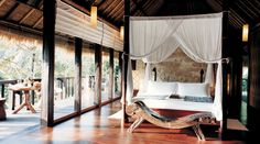 Stone wall behind canopy bed and primitive wood chaise in the Tejasuara suite at COMO Shambhala