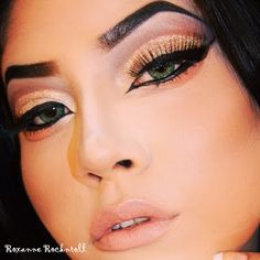 It's all about the eyes in this makeup look! Nude cheeks and lips serve as subdued counterpoints while bronzed glitter, black winged liner all around, and a blackened brow capture all the attention.