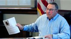 Maine Gov. Paul LePage holds up news release with a booking mug shot from a three-ring binder of news releases and articles about drug arrests during a meeting with reporters on Friday, Aug. 26, 2016,