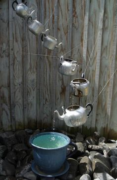 multiple tea kettles pouring into pot on grounds,  tea pots water fountains, back yards outdoor old fashioned water faucets,  Well isn't that the most clever lil fountain!  Adorable!