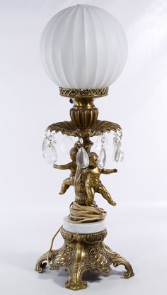 Lot 695: Cast Metal Electric Cherub Table Lamp; Having a milk glass globe, gilt metal dancing cherubs, marble plinth and Rococo style base with cut glass prism accents