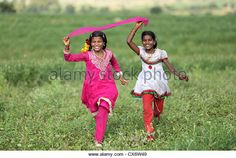 Indian girls running in a field Andhra Pradesh South India - Stock Image