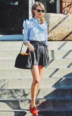 Taylor Swift's red lips and loafers add a pop if color to a button down and leather skater skirt. #street #style