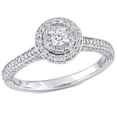 This lovely double halo engagement ring is crafted in 14-karat white gold and features a single prong-set diamond at the center with 160 pave-set diamonds surrounding it. This ring is the perfect choice for today's trendsetting woman.  The center stone shape is Round, diamond color is GHI and clarity is I1-I2