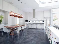Bathed in sunlight from a wall of windows and a skylight, this modern open-plan kitchen and dining room are tied together by a stained concrete floor. Pendant lighting in copper and a wood dining room table add welcome color and a contrast of finish. Concrete Kitchen Floor, Concrete Floors, Kitchen Flooring, Stained Concrete, Kitchen Tile, Cement Counter, Kitchen Worktops, Farmhouse Flooring, Laminate Counter