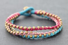 This is Hand Woven bracelet made with blue ,light pink and shocking pink cotton waxed cord weaved together with brass bead . Closure using brass bell