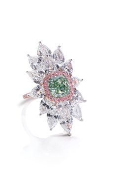 A cushion-shaped Green Diamond highlighted by Pink pave diamonds and mounted with pear-shaped White Diamonds totaling 11.08 carats.