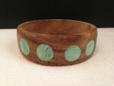 Beautiful and unique wooden bangle bracelet with round, green acrylic inlays. This bracelet appears to have been hand make and reminds me of maybe