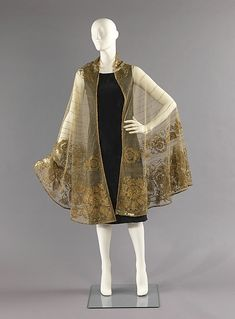 Evening cape, 1935, Mae & Hattie Green. This evening cape is an excellent representation of the glamour associated with the 1930s. Although it is a French-made piece, the flowers allude to Spanish floral forms, seen in Spanish lace and embroidered shawls.