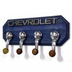 car part furniture Chevrolet Coat Rack Chevy Hat Rack with 4 Chrome by StarlingInk, can do this with my spare parts! Car Part Furniture, Automotive Furniture, Automotive Decor, Furniture Plans, Kids Furniture, Garage Furniture, Wall Hat Racks, Diy Hat Rack, Rack Shelf