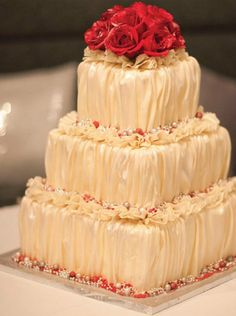 Ruched champagne fondant cake with red fondant roses and ruffles. Design by www.desserttrends.ca. See more of Marianna's wedding - http://www.canadianbride.com/articles/marianna-tsenhlevych--tenny-tsang