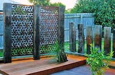 Rusted steel and railway sleeper screen to block view to neighbour's house.